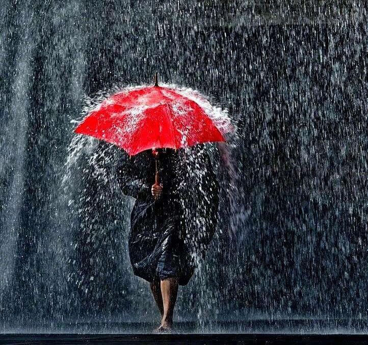 Woman holding a red umbrella & walking in the rain